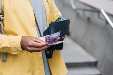 cropped view of mixed race man holding wallet while counting euro banknotes 写真素材
