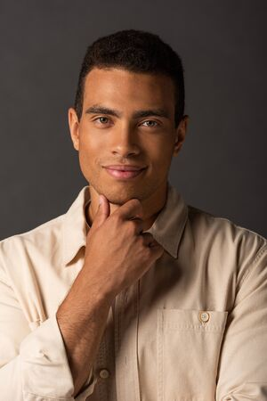 portrait of smiling handsome mixed race man in beige shirt on black background