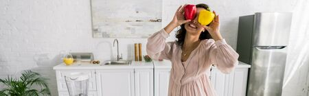 panoramic shot of happy woman holding red and yellow paprika Stok Fotoğraf