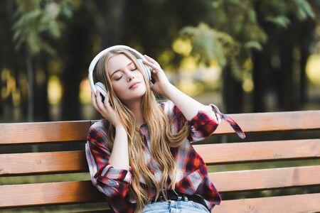 beautiful girl in casual clothes listening to musing on headphones and looking away while sitting on wooden bench in park
