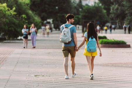 back view of man and woman with backpacks walking and holding hands