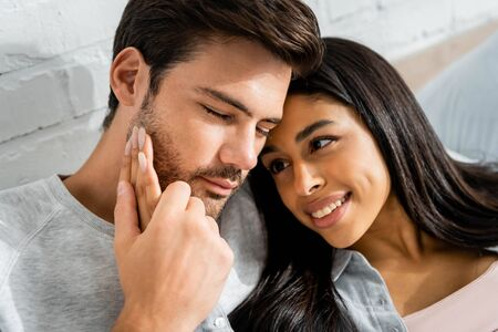 handsome man hugging smiling african american woman in apartment
