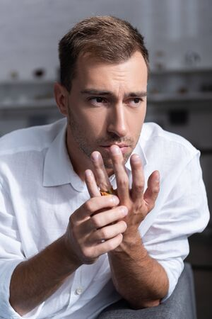 depressed man with ring looking away at home