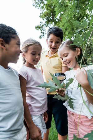 happy multicultural kids looking at green leaves though magnifier Stock Photo