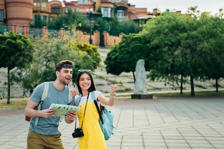 handsome man holding map and asian woman pointing with finger