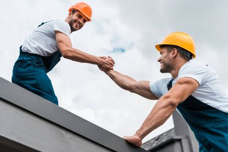 low angle view of cheerful handymen in helmets holding hands