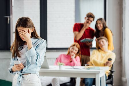 Gruppe von Schulkindern, die über trauriges Mädchen mit Smartphone lachen