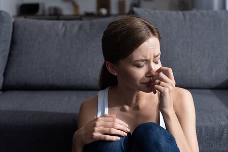upset young woman with ring sitting near sofa and crying at home