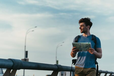 smiling and handsome man in t-shirt and shorts holding map and looking away