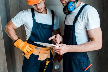cropped view of bearded repairman pointing with finger at digital tablet near coworker