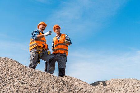 selective focus of coworkers in orange helmets standing on rocks against sky Reklamní fotografie