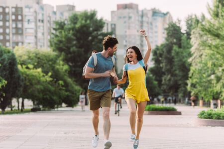handsome man and asian woman running and showing yes gesture