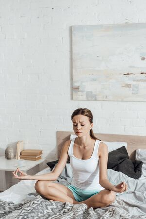 upset young woman sitting on bed in lotus pose with closed eyes
