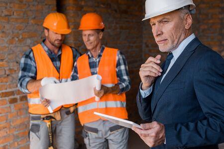 selective focus of mature businessman holding digital tablet near architects Reklamní fotografie
