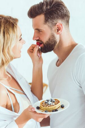 young sensual woman feeding boyfriend with strawberry while holding plate with pancakes