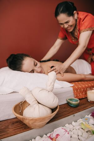 selective focus of herbal balls and asian masseur doing hot stone massage Stock Photo