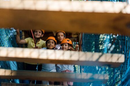 selective focus of happy multiethnic kids near high rope trail