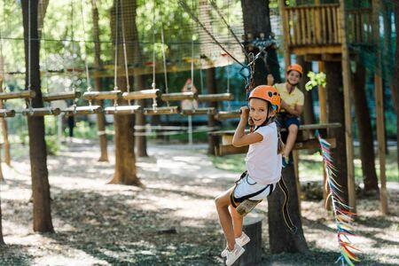 selective focus of cute kid near adorable boy in adventure park