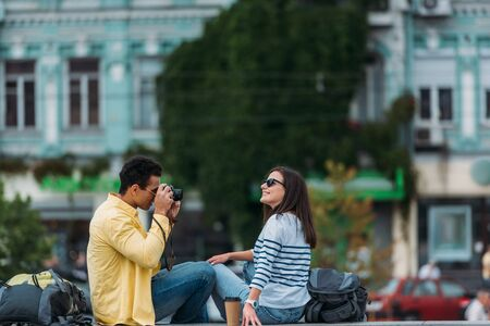 Bi-racial man sitting and taking photo of woman in sunglasses with backpack Фото со стока