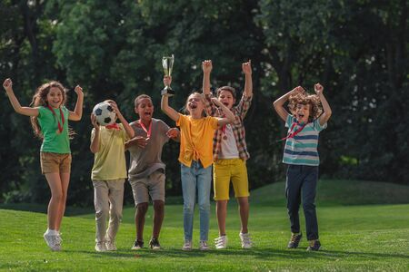 happy multicultural kids football and trophy in park Фото со стока