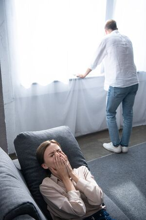 upset woman crying on sofa and man standing near window
