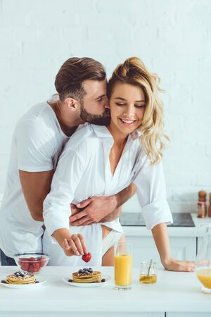 handsome man hugging and kissing beautiful girlfriend while standing near table with served breakfast