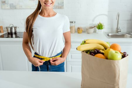 cropped view of cheerful young woman measuring waist near paper bag with groceries 写真素材