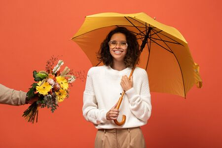 boyfriend gifting happy woman with umbrella bouquet of flowers isolated on orange