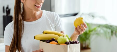 panoramic shot of positive  woman looking at lemon near paper bag with fruits