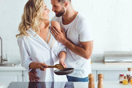 handsome young man hugging cheerful girlfriend preparing breakfast on frying pan