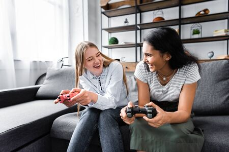 KYIV, UKRAINE - JULY 10, 2019: multicultural friends sitting on sofa and playing video game in apartment Фото со стока