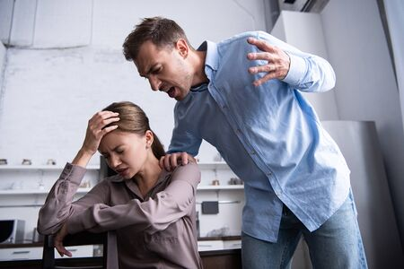 aggressive man in shirt screaming at scared wife at home Banco de Imagens