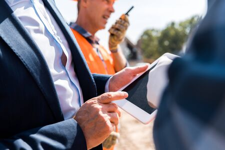 cropped view of businessman pointing with finger at digital tablet near architects