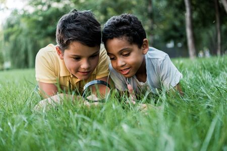selective focus of multicultural boys lying on grass and looking through magnifier Фото со стока