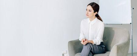 panoramic shot of attractive journalist in formal wear sitting in armchair 版權商用圖片