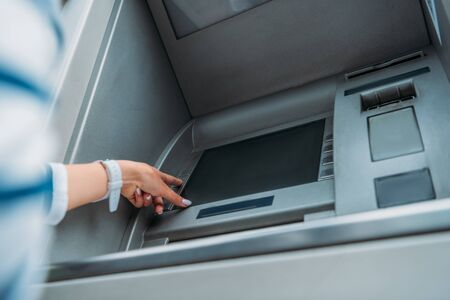 low angle view of woman pressing button on atm machine Foto de archivo