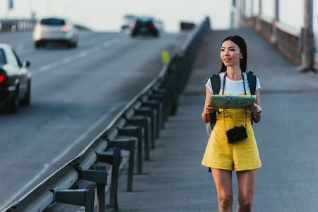 asian and beautiful woman in overalls holding map and looking away 스톡 콘텐츠