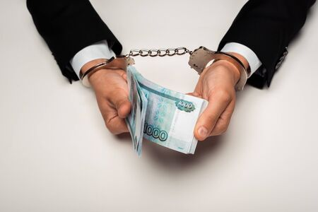 top view of businessman in handcuffs holding bribe on white