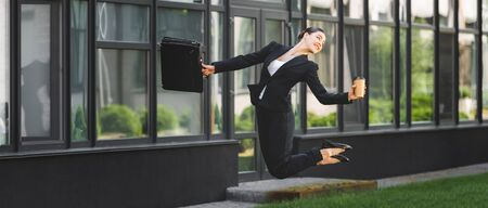 panoramic shot of happy businesswoman levitating while holding paper cup and briefcase