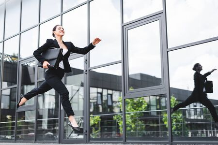 happy businesswoman levitating on street while holding briefcase Stok Fotoğraf