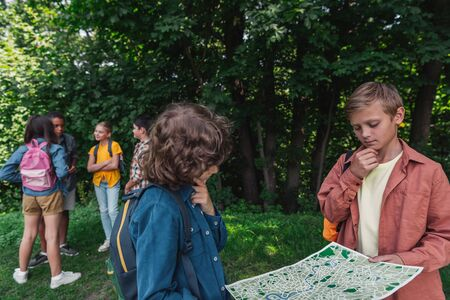 selective focus of pensive boys holding map near friends