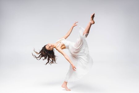 young beautiful ballerina in white dress dancing on grey background