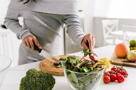 cropped view of woman holding knife near broccoli and paprika