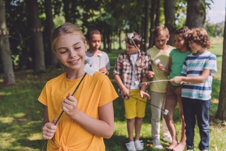 selective focus of happy child looking at sweet marshmallow on stick near multicultural friends