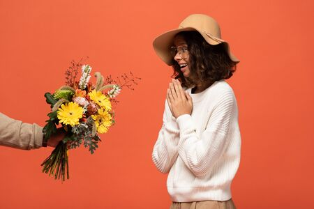 boyfriend gifting surprised woman in hat bouquet of flowers isolated on orange