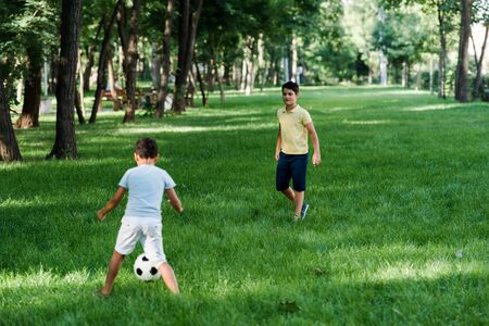 cute multicultural boys playing football on grass