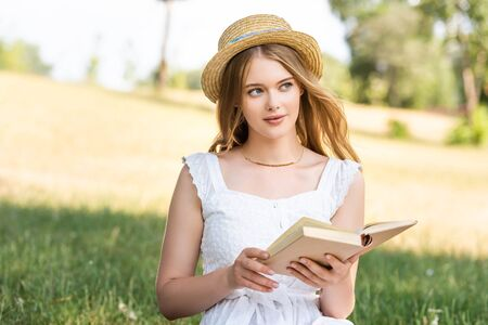beautiful girl in white dress and straw hat holding book while sitting on meadow and looking away Zdjęcie Seryjne