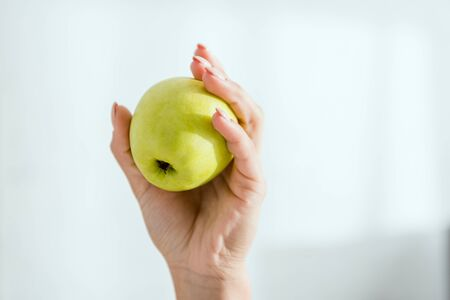 cropped view of young woman holding green organic apple