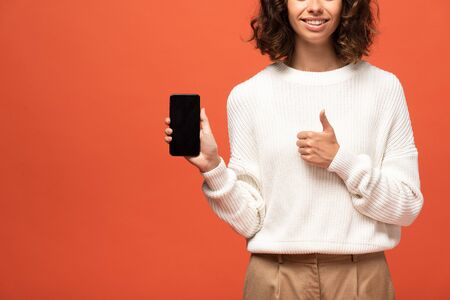 cropped view of woman in autumnal outfit holding smartphone with blank screen and showing thumb up isolated on orange