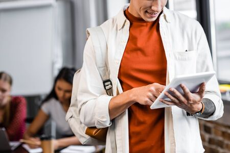 cropped view of handsome student in shirt using digital tablet in apartment